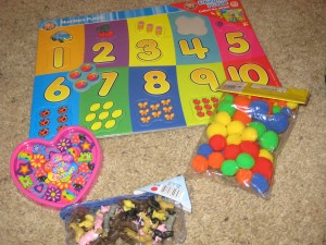 A number/counting puzzle, mini-farm animal counters, Lisa Frank mini-erasers and Pom-Poms