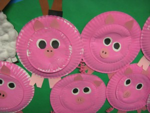 These are paperplate pigs. We painted an 8-inch and 5-inch paper plate pink.  Then we added feet, ears, eyes and a snout out of construction paper.  We used  pink pipe cleaners to create their curly tails!